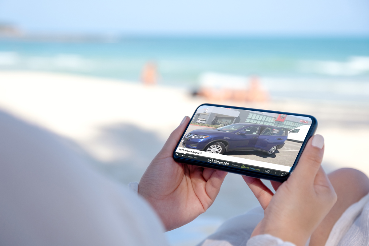 Woman watching a Video 360 video when shopping for a car on her SmartPhone on a beach